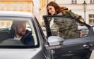 Frau steigt in Auto ein