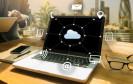 Laptop auf Tisch mit Cloud-Computing-Symbolen
