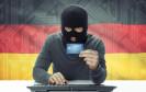 Hacker mit Kreditkarte vor Deutschlandflagge