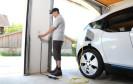 Mann steckt E-Auto an die Ladesäule
