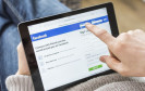 Person surft auf Facebook mit Tablet